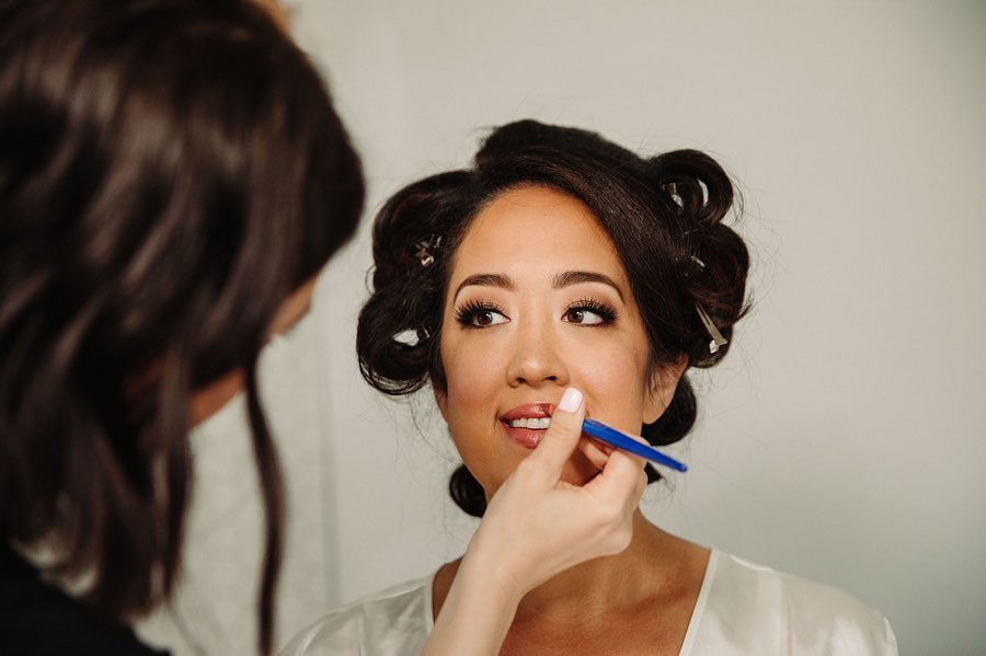 A close up portrait of a woman as lipstick is applied to her lips by a makeup artist in a Milwaukee Wisconsin wedding