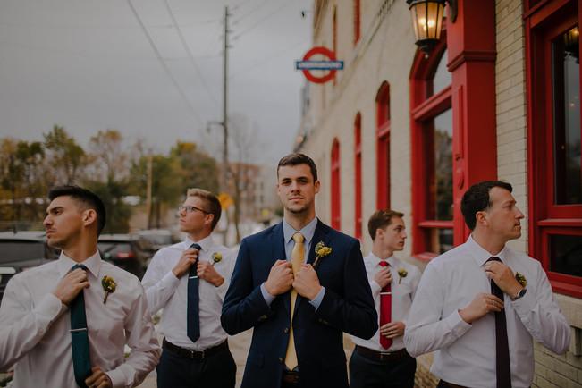 A groom and groomsmen pose for the camera near Kadish Park