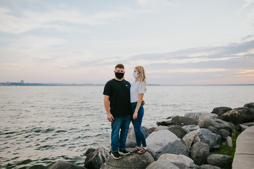 A man and woman wear masks during their downtown Madison engagement session