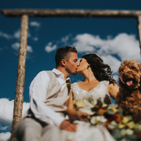 A man and woman share a kiss next to their dog in a Winter Park, Colorado wedding