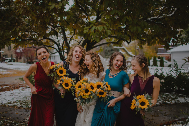 A bridal party links arms and laughs at each other in front of a large tree during a wedding in Milwaukee