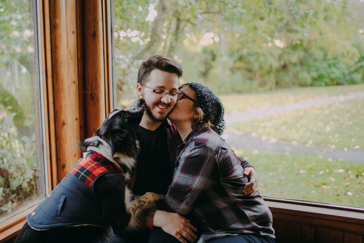 A dog and a woman kiss a mans' face at a Peninsula State Park engagement session