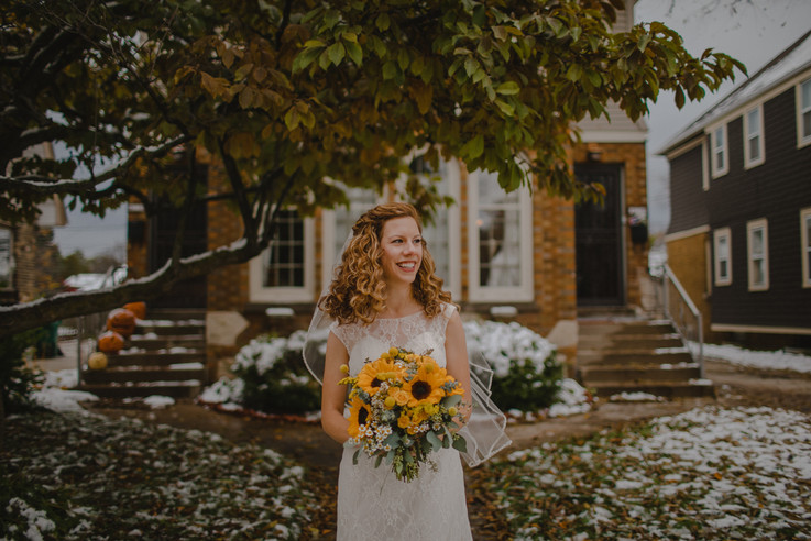A bride laughs and smiles under a tree in a Milwaukee park