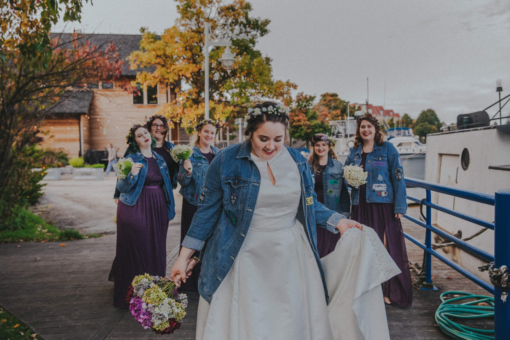 A wedding party laughs together as a bride walks towards the camera on the docks of the Sheboygan River