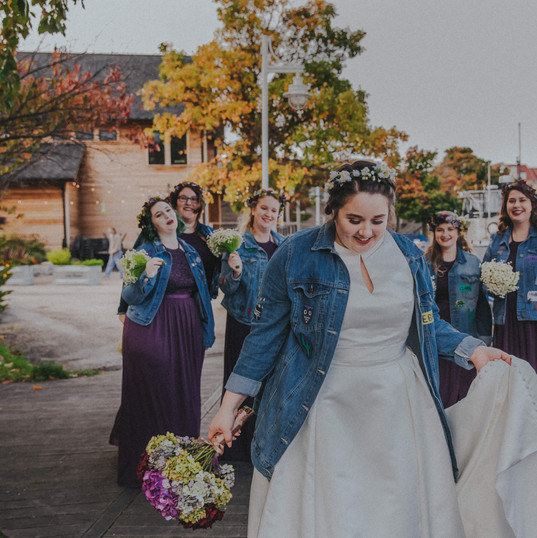 A bride and her bridesmaids walk on the Sheboygan riverwalk at a fall Sheyboygan wedding