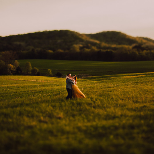 A man and woman embrace at sunset in a farm field in a La Crosse, Wisconsin engagement session