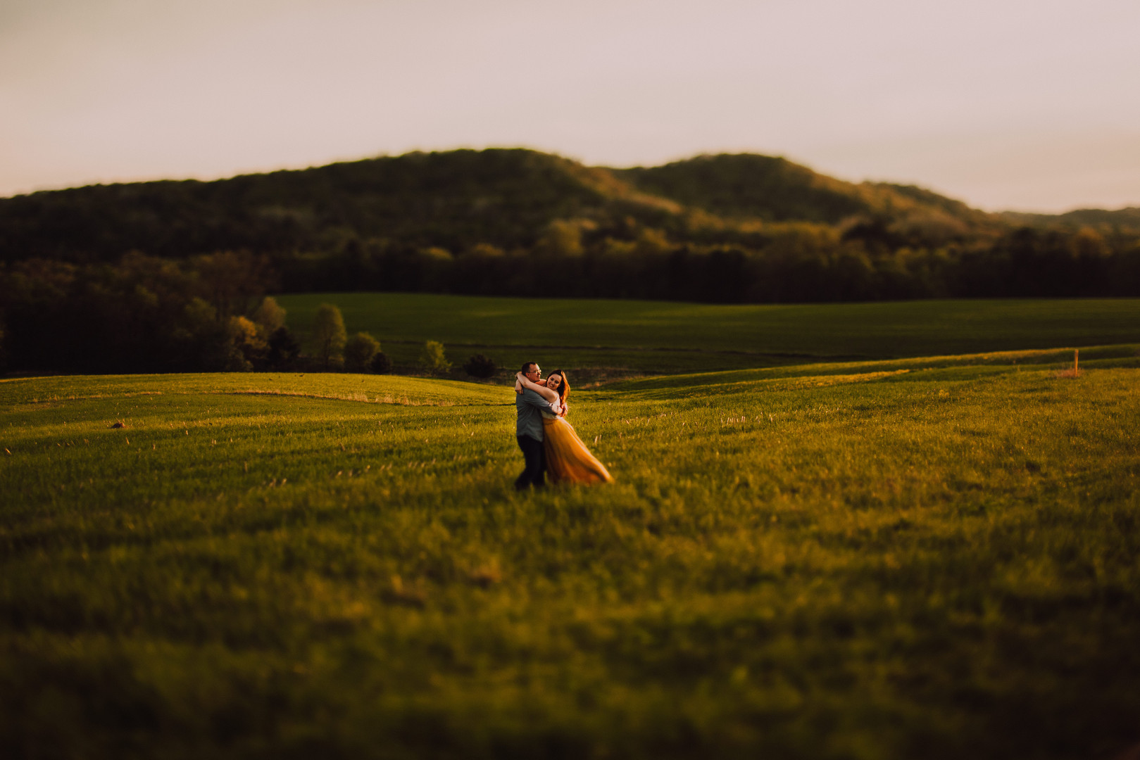 A man and woman dance at sunset on hilly farm fields in Kickapoo Wisconsin