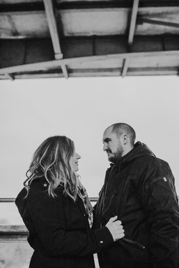 A man and woman look at each other during Milwaukee engagement photos