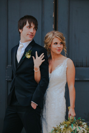 A bride and groom pose in front of a door