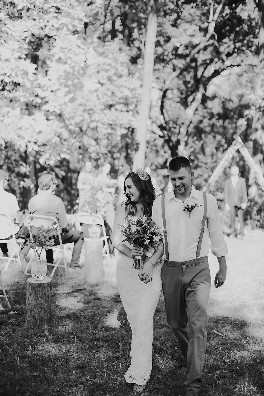 A bride and groom walk down the aisle at the backyard Milwaukee wedding