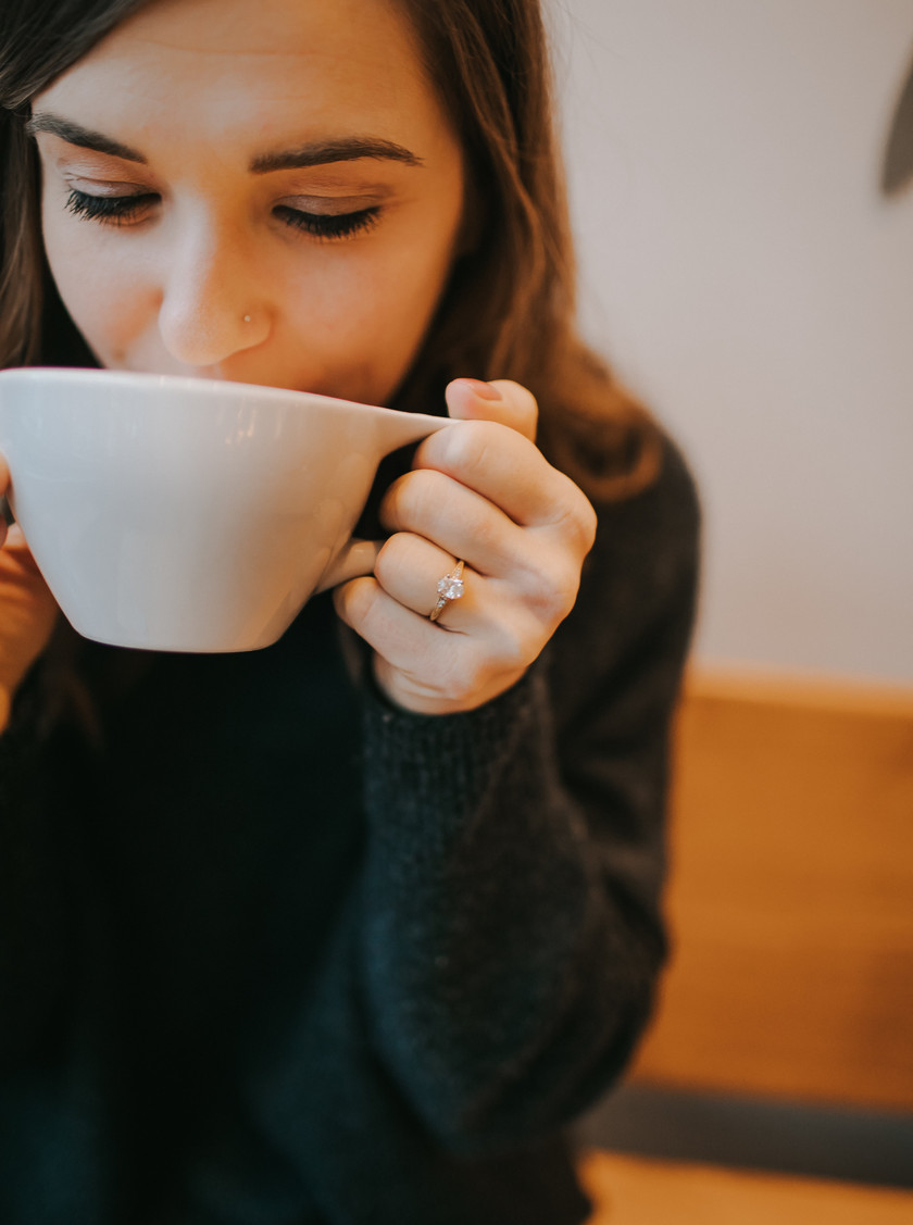 A close up of a woman's engagement ring as she drinks from a coffee mug in Milwaukee engagement photos