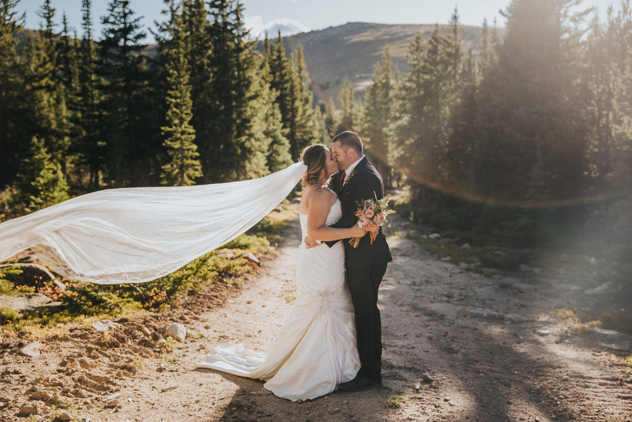 A bride and groom kiss on a dirt road at a Winter Park Resort wedding