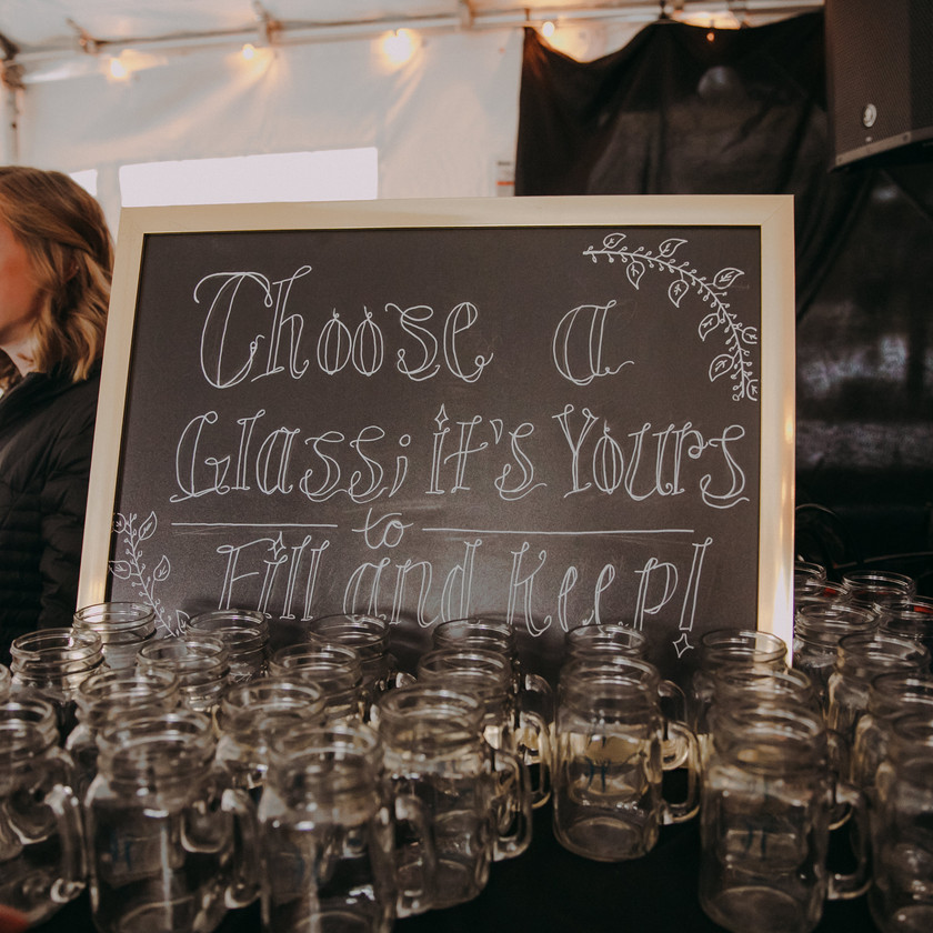 A table at the Red Lion Pub, filled with mason jar mugs and a sign telling guests to choose a mug to keep