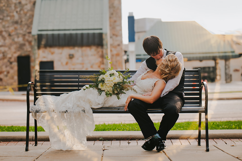 A man and a woman kiss on a bench in downtown Oshkosh wedding photos
