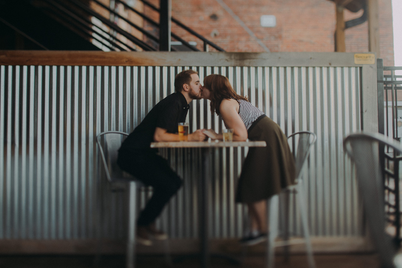 A man and woman reach across a table to kiss at Guu's on Main in Downtown Stevens Point, Wisconsin