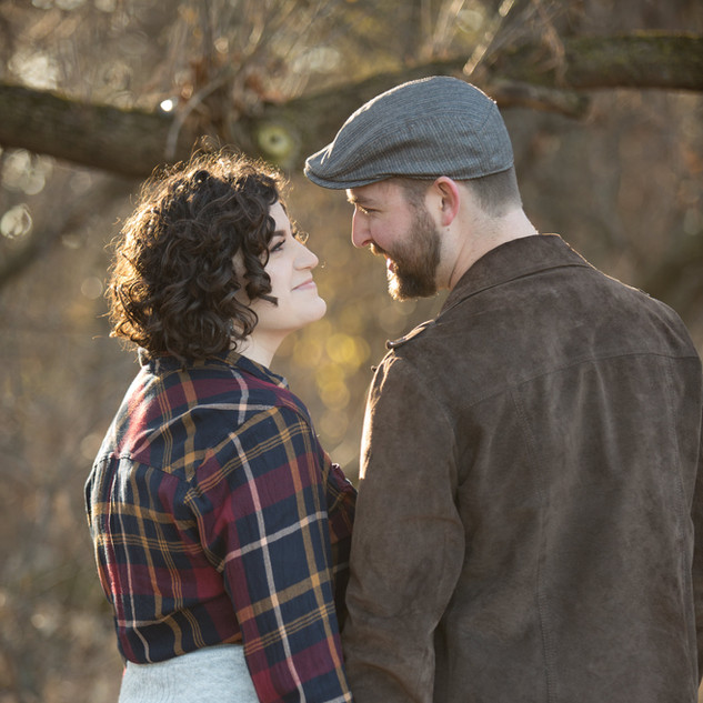 A woman and a man gaze at each other in the woods in Stevens Point Wisconsin