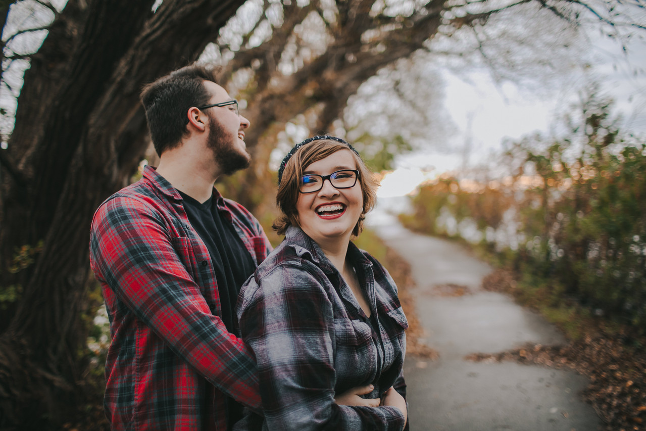 A woman laughs at the camera as a man holds her from behind at a Peninsula State Park engagement session in Door County