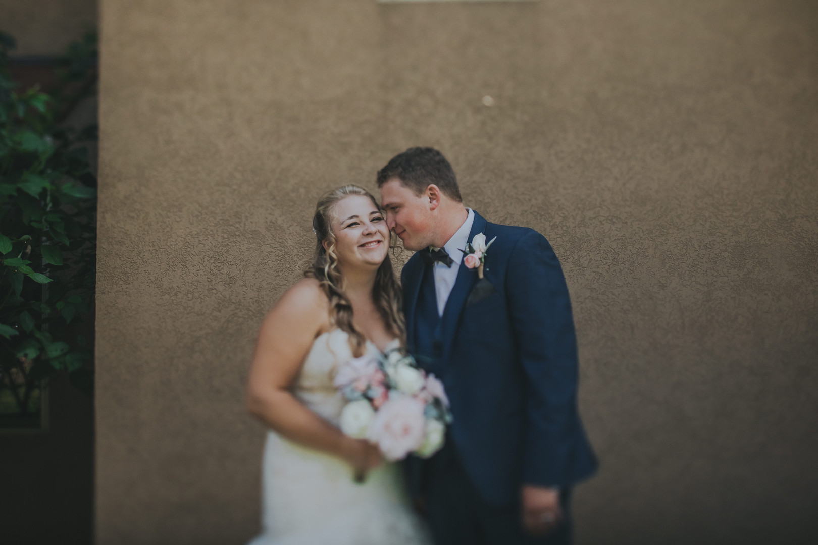 A groom nuzzles a smiling bride on the cheek at an intimate wedding in Stevens Point Wisconsin