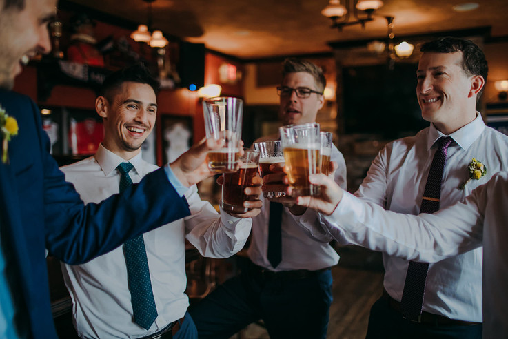 A group of mens cheers their beer glasses together during a Wisconsin wedding