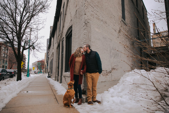 A woman and man kiss against the corner of a historic Milwaukee building