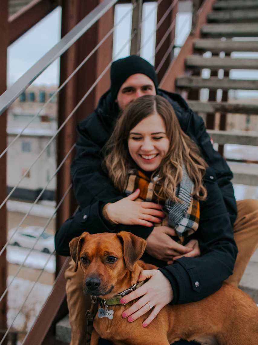 A dog and two people sit on stair in a Milwaukee engagement session