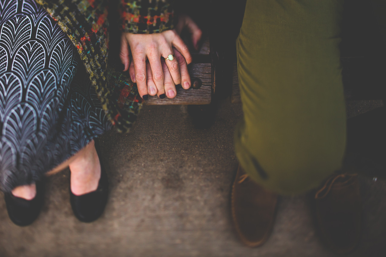 A close up of an opal engagement ring from above as a man and woman hold hands on a park bench in Downtown Colorado Springs, Colorado