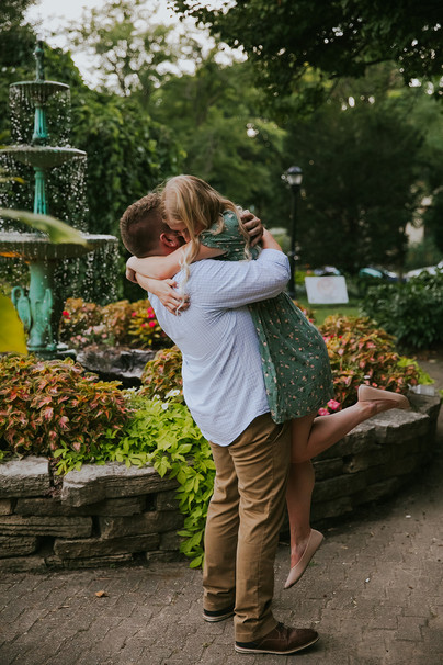A couple embrace in front of a fountain in Period Garden Park