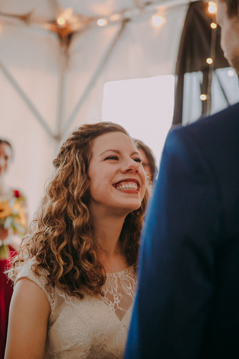 A bride smiles at her groom as they say their vows