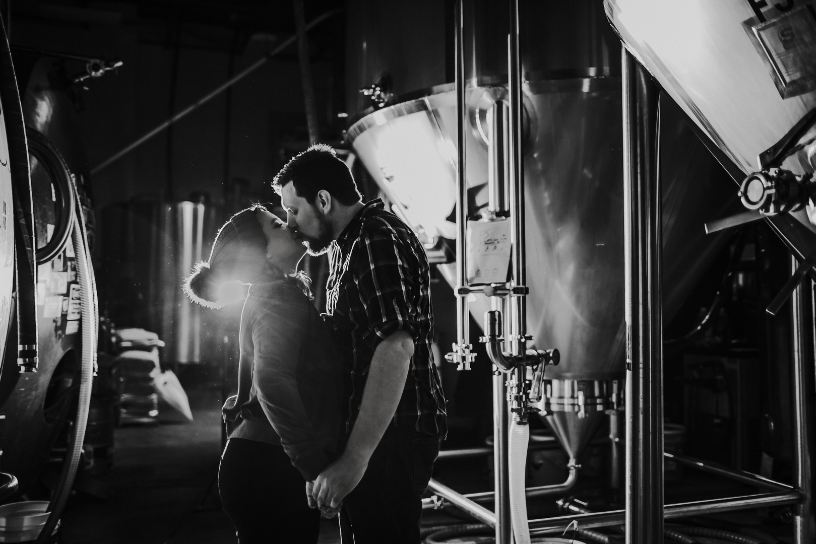 A woman and man kiss in front of beer tanks at O'so Brewing in Plover Wisconsin