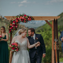 A man and woman touch noses as they walk down the aisle at The Manor House Wedding in Littleton, Colorado
