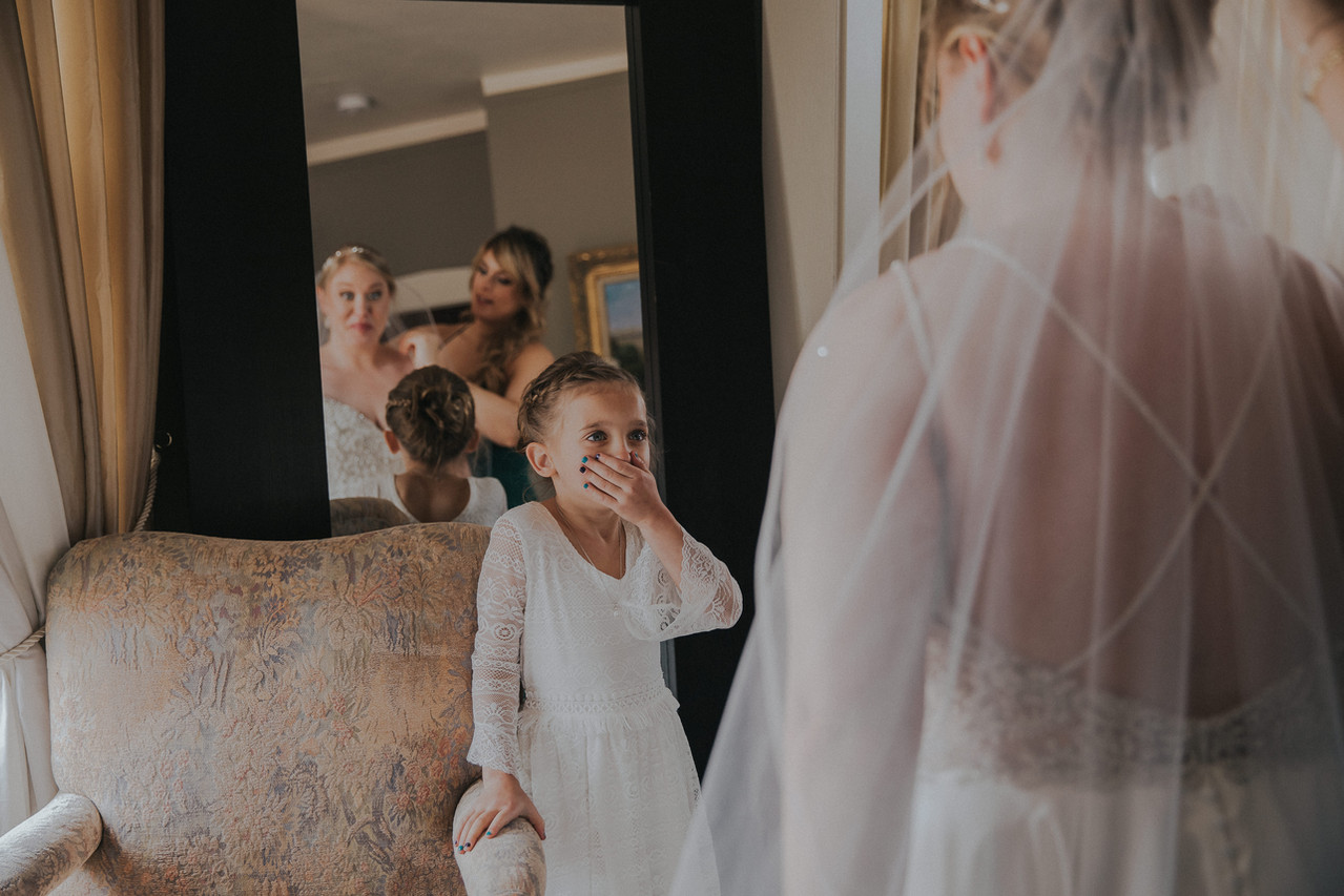 Flower girl places hand over mouth in admiration as she looks at the bride at The Manor House in Littleton, CO