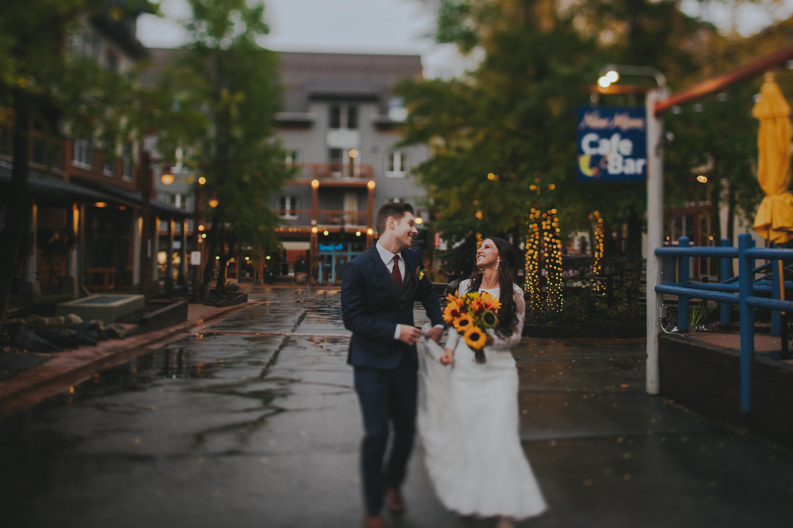 A bride and groom laugh together as they walk together during their Warren Station wedding at the Keystone Resort