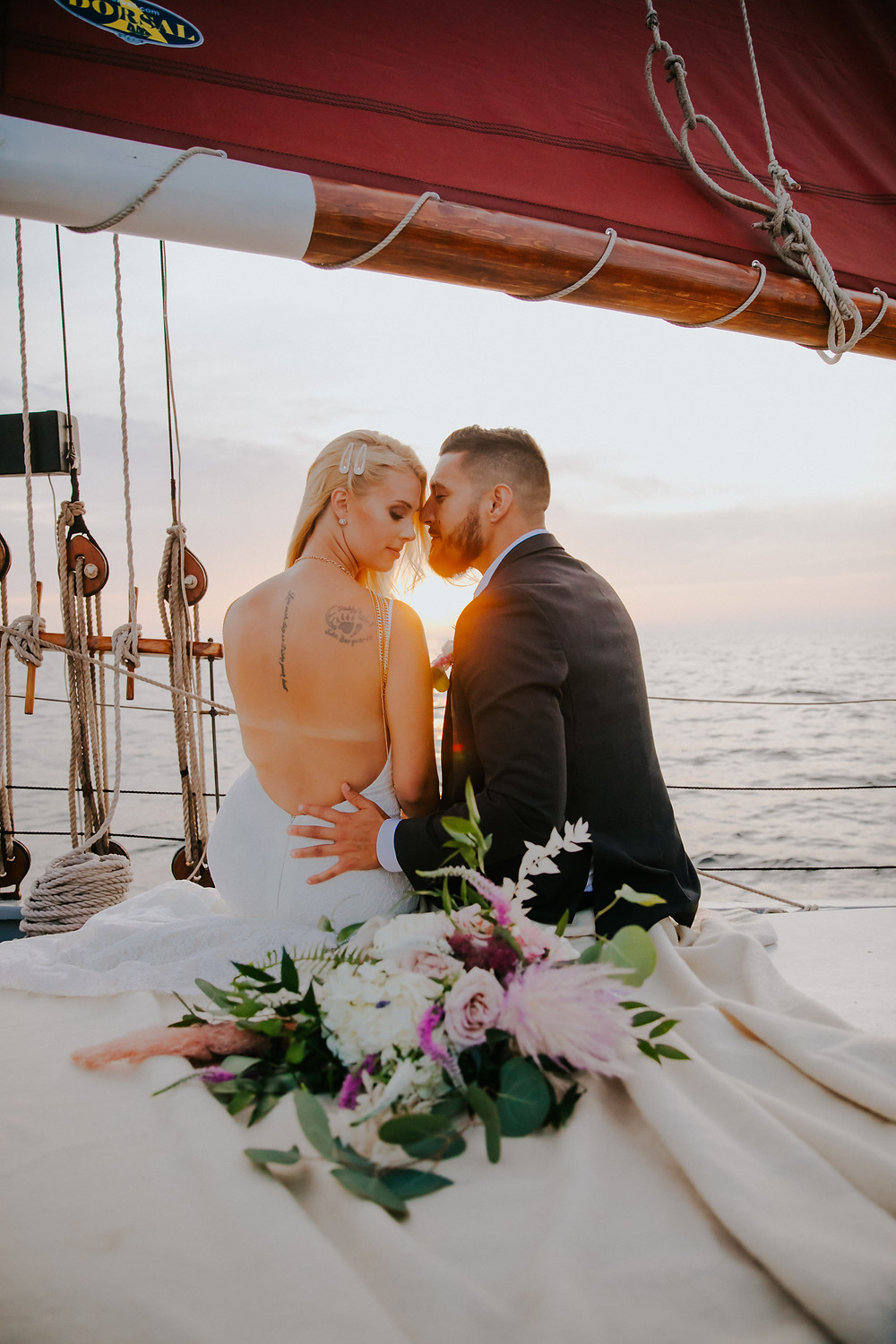 A man and woman cuddle together on a sunset sailboat ride with Sail Door County - Door County Wedding Photographer