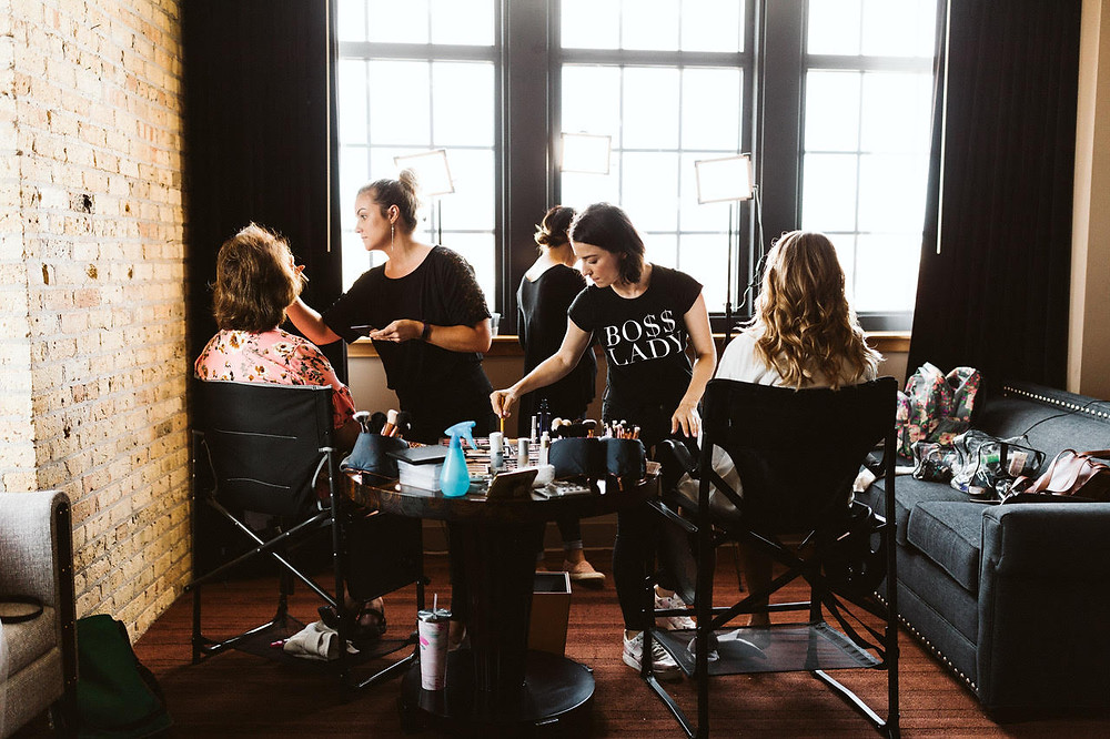 A group of women sit in chairs while getting their makeup applied by Melody Sopa Artistry in a Milwaukee Wisconsin wedding