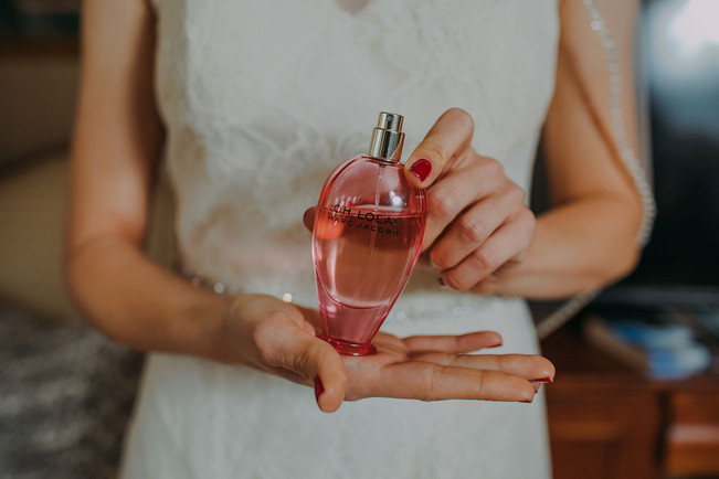 A bride holds a perfume bottle
