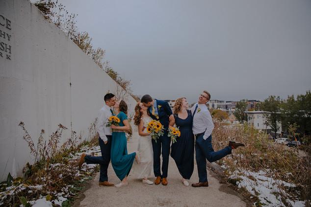 A wedding party poses on a walking path at Kadish Park