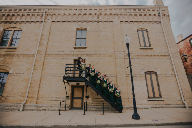 A wedding party poses on staircase in Downtown Oshkosh