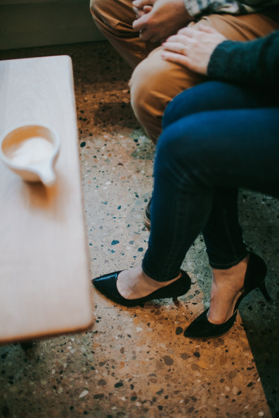 A close up of a woman's high heels as she sits next to a man