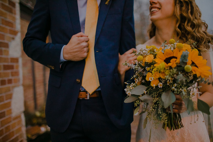 A close up of a bride holding a bouquet and a groom holding his suit in Milwaukee