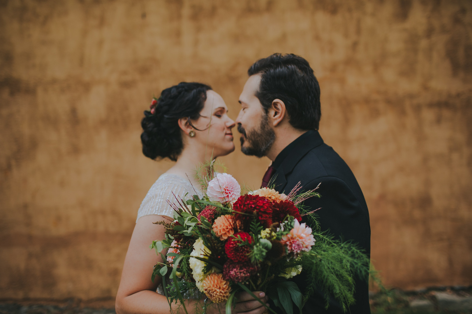 Close up of a bride and groom kissing in front of the Pfiffner Building in Stevens Point, WI