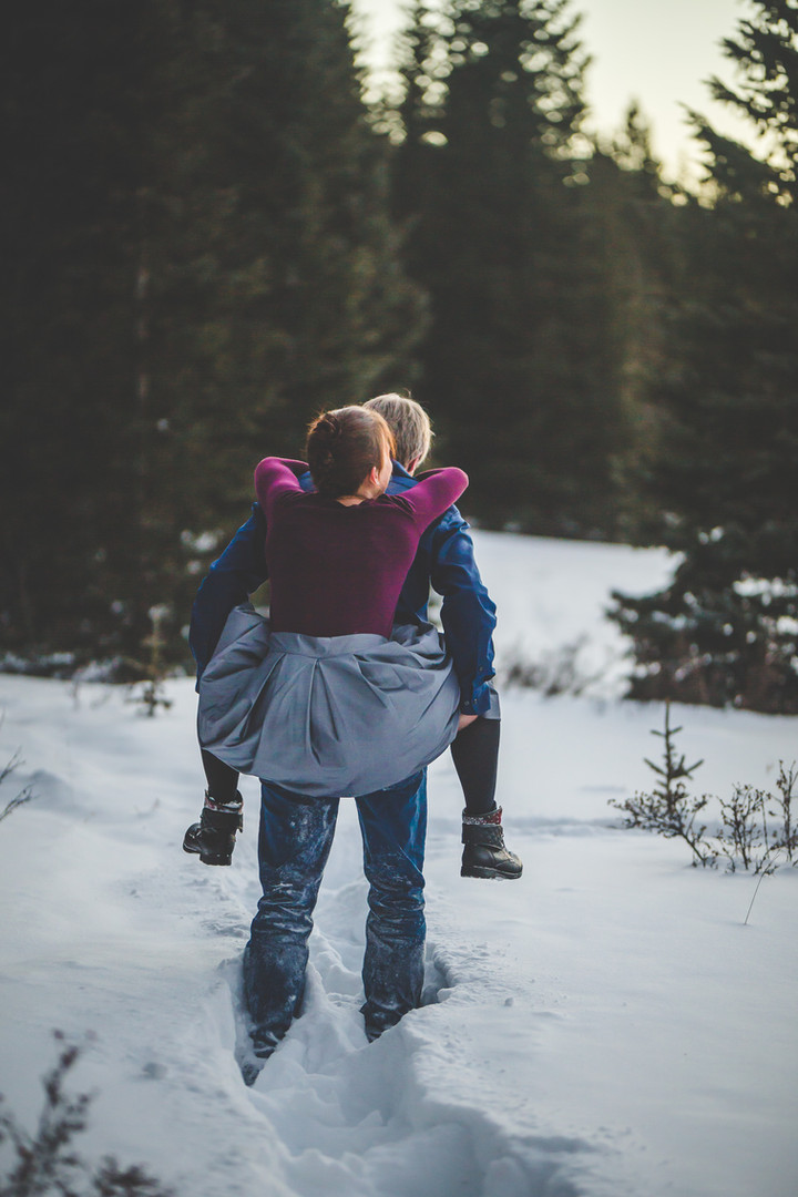 A man give a woman a piggy back ride in a snowy forest at a Horsethief Falls engagement session