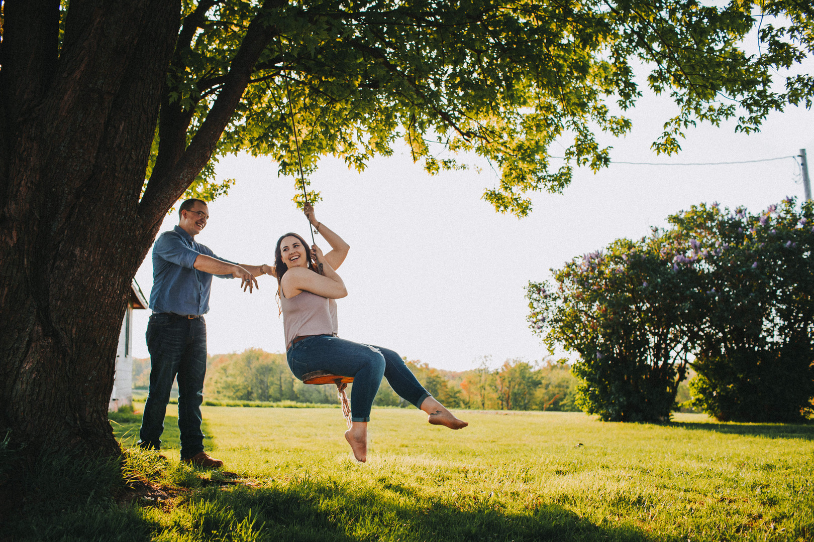 A man pushes a woman on a swing during a Madison, Wisconsin engagement session