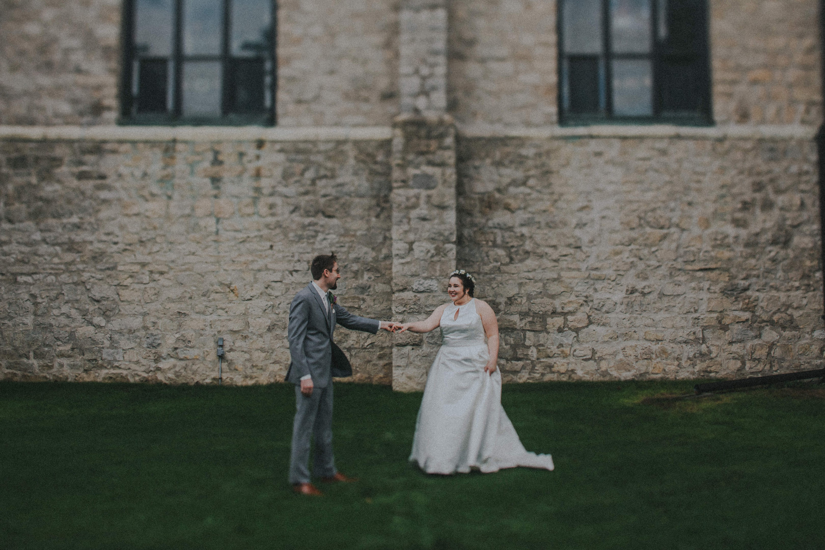 A groom and bride reach their hands towards each other in front of Holy Name of Jesus Catholic Church - Mary Petrie in Oshkosh Wisconsin
