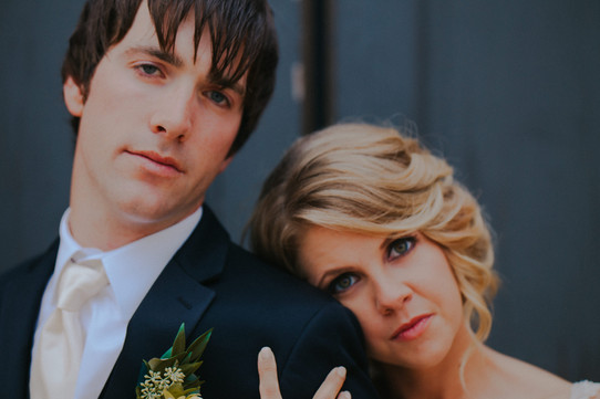 A close up of the bride and groom looking into the camera