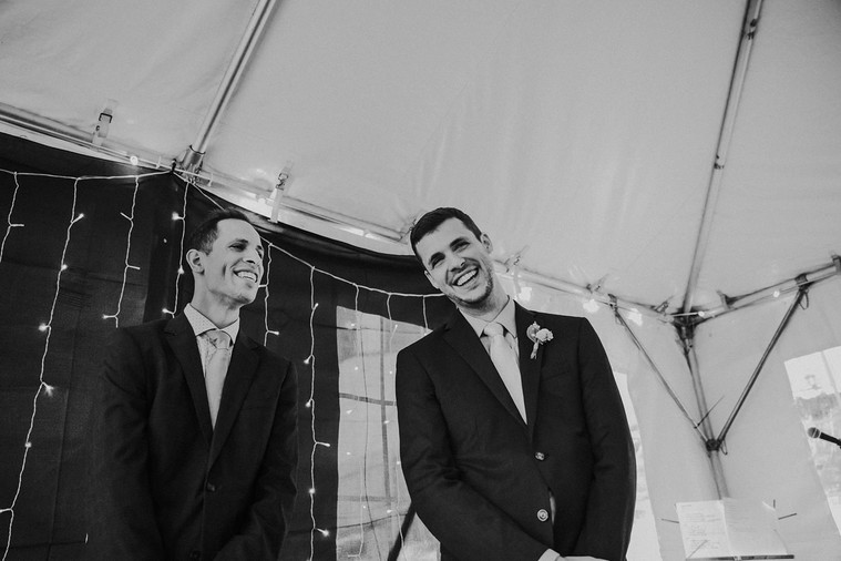 A groom and officiant laugh together during a Milwaukee wedding ceremony