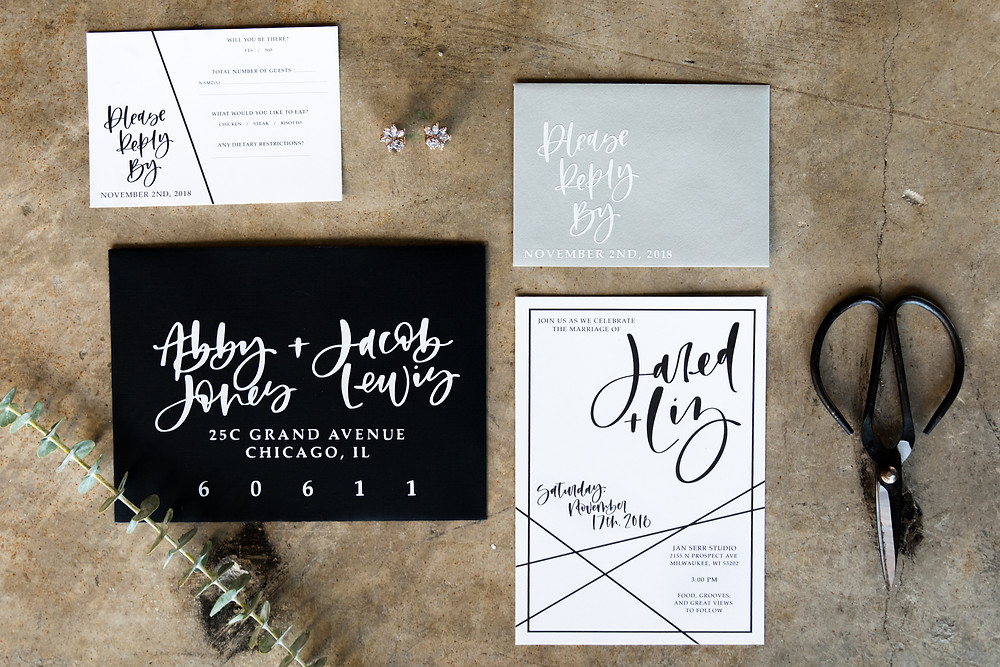 A flat lay of envelopes and wedding invitations on concrete in Milwaukee Wisconsin