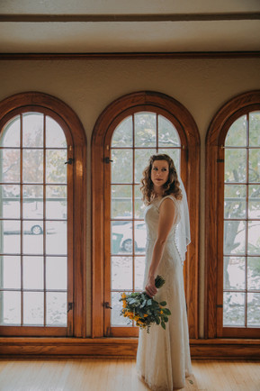 A bride stands in front of a wall of windows in a Milwaukee Air BnB