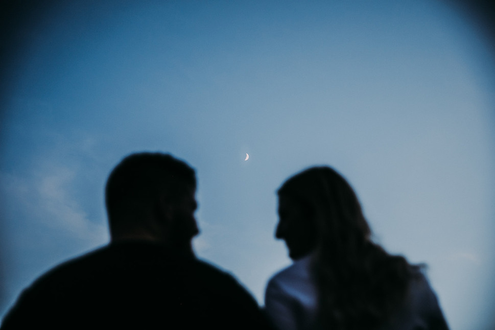 A man and woman gaze at each other with the moon between them