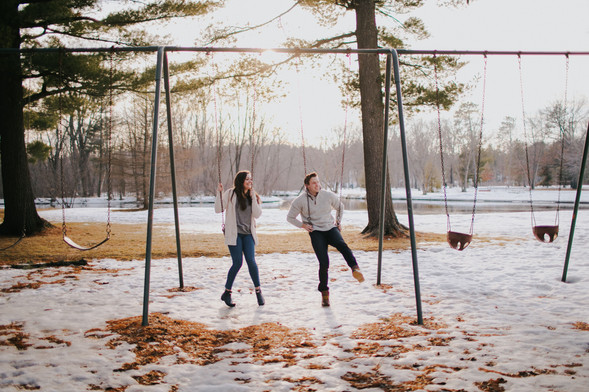 A man and woman sits on a swingset during Stevens Point engagement photos at Iverson Park