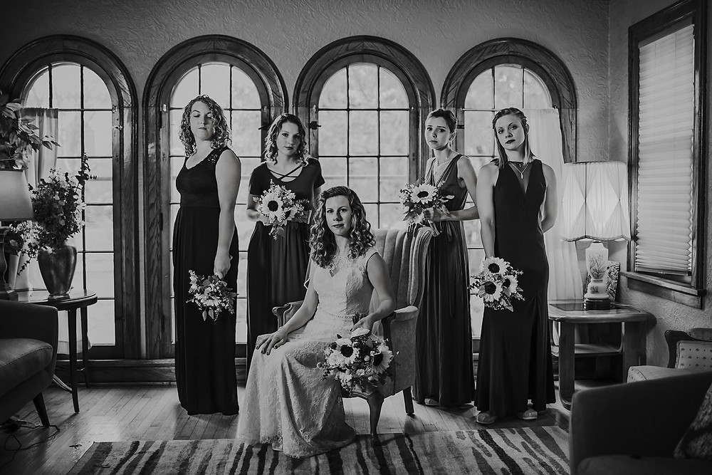 A bride and bridesmaid pose in front of tall windows in downtown Milwaukee, Wisconsin